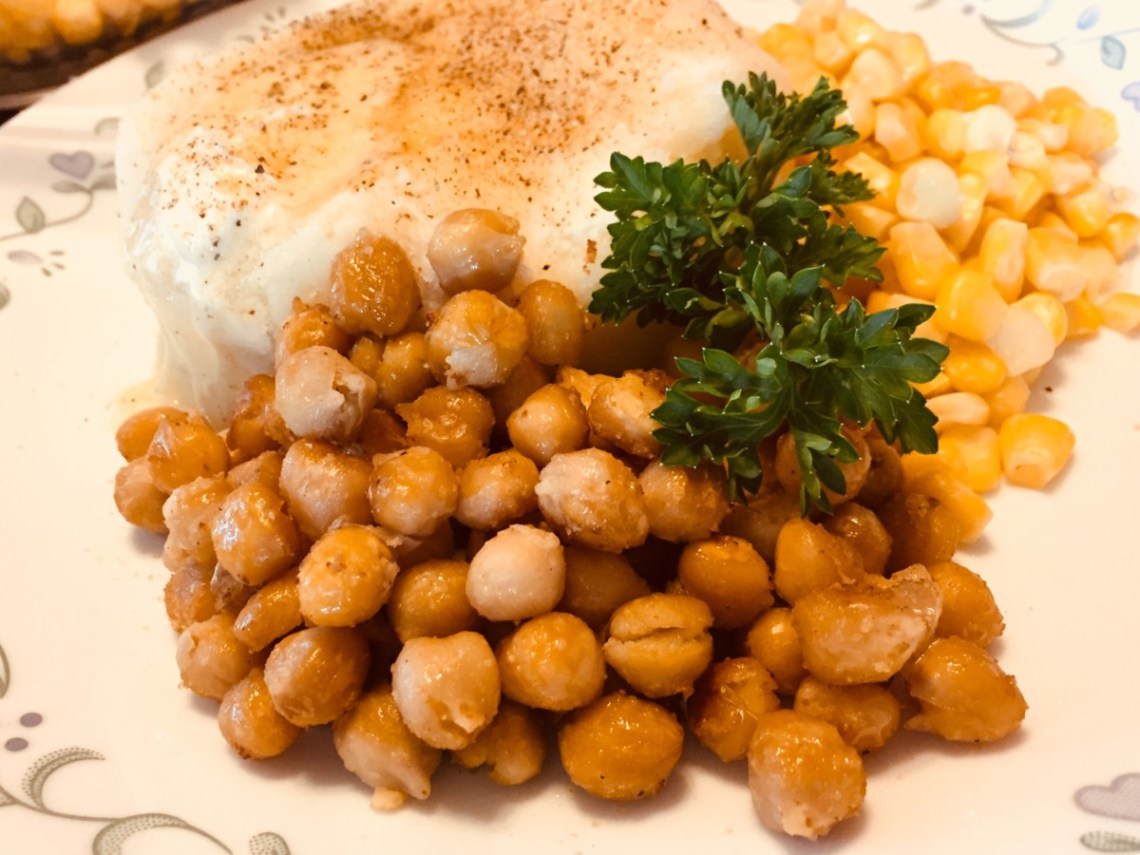 Image shows Fast Pan-Fried Chickpeas-an Easy Main Dish. The chickpeas are golden brown and featured in the foreground. Behind them is a sprig of parsley, yellow sweet corn, and creamy mashed potatoes with vegan butter and seasoning salt on top.