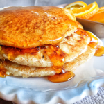 Fluffy vegan whole wheat pancakes shown with syrup running off the stack