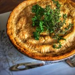 Chickpea pot pie shown on a plate garnished with parsley and thyme