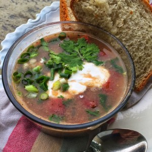 Easy black bean soup being shown with a side of homemade bread, garnished with cashew sour cream, cilantro and green onions Yummy!!