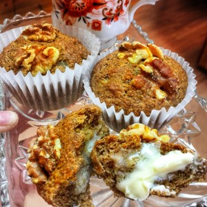 Vegan Banana Nut Muffins shown on a glass plate with a cup of tea in the background