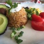 Shown plated beside and avocado half and a red tomato