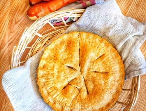 Pie shown in a wicker basket with carrots