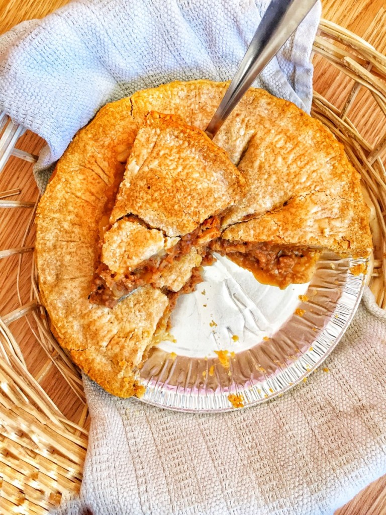 Tourtiere shown with a slice placed on top of the pie