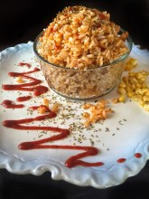 Vegan Mexican Fried Rice shown in a clear glass bowl, surrounded by swirls of hot sauce and corn