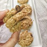 Vegan oatmeal chocolate chip cookies shown stacked between fingers, ready to eat!