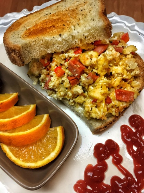 Tofu scramble shown sandwhiched between two pieces of bread, plated beside sliced oranges and a line of ketchup