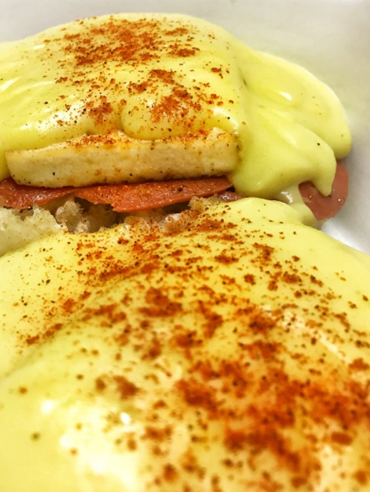 Two vegan eggs benedict smotherd in hollandaise sauce and sprinkled with smoked paprika