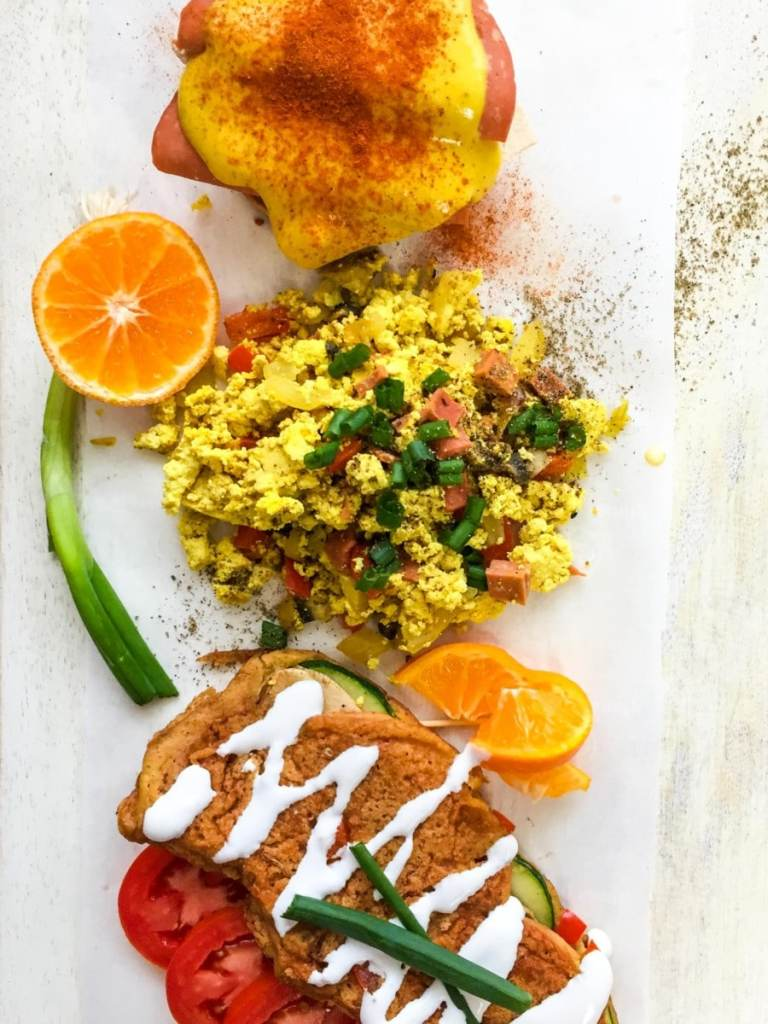 Vegan Tofu Scramble shown on a white plate with green onions cut on top, chickpea omelette, and vegan eggs benedict