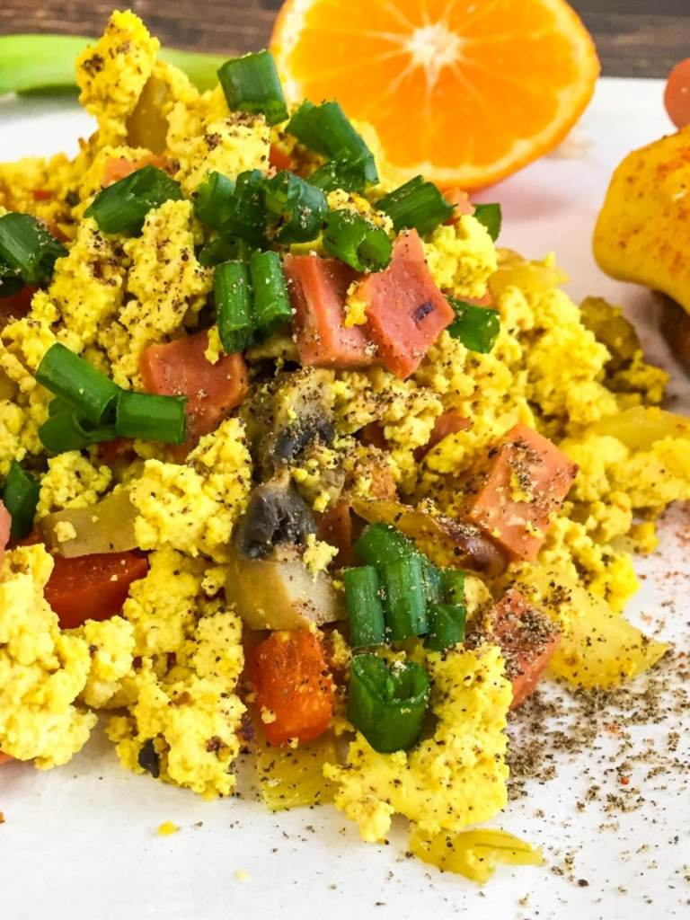 Vegan Tofu Scramble shown on a white plate with green onions cut on top