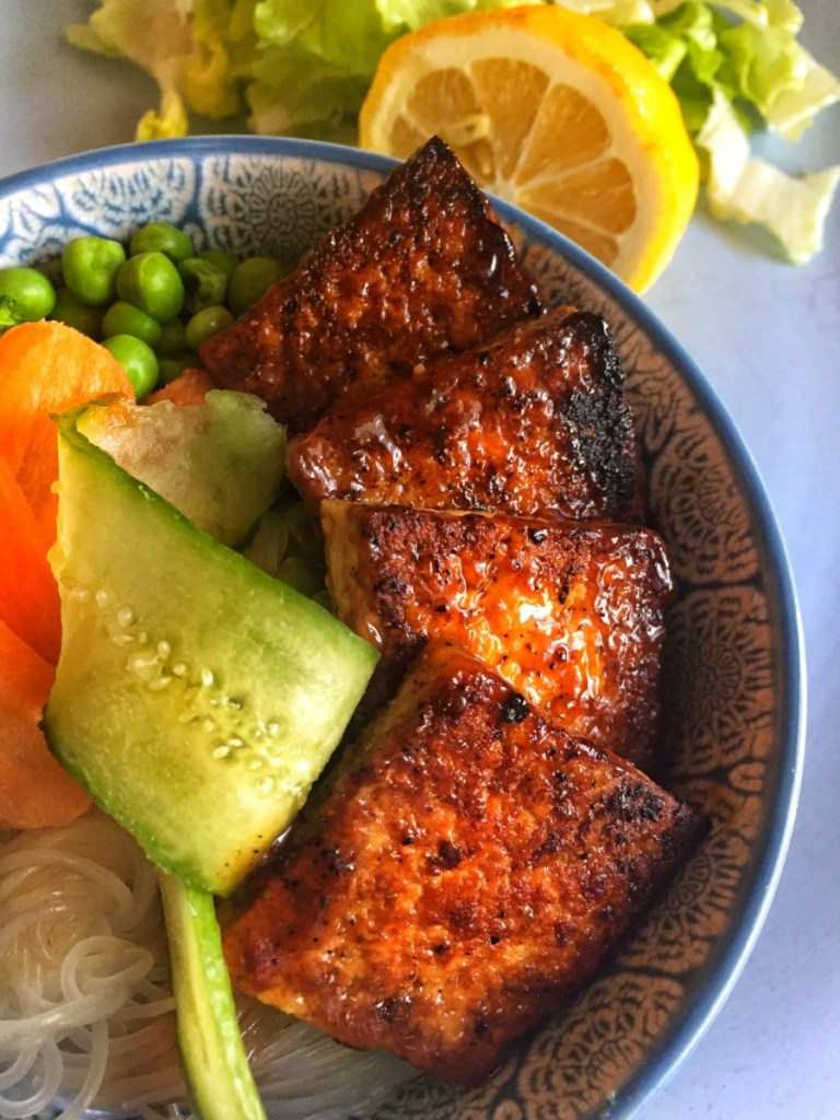 Teriyaki Tofu Vermicelli Bowl Shown in a blue boel topped woth cucumber, shredded carrot, broccoli and green peas