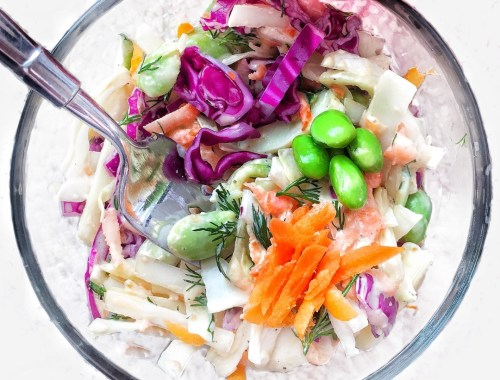 Healthy Vegan Coleslaw with Edamame and Dill shown in a small meal prep bowl with a fork ready to eat