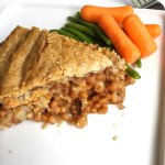 Vegan lentil pot pie shown with a slice on a white plate with a side of carrots and green beans