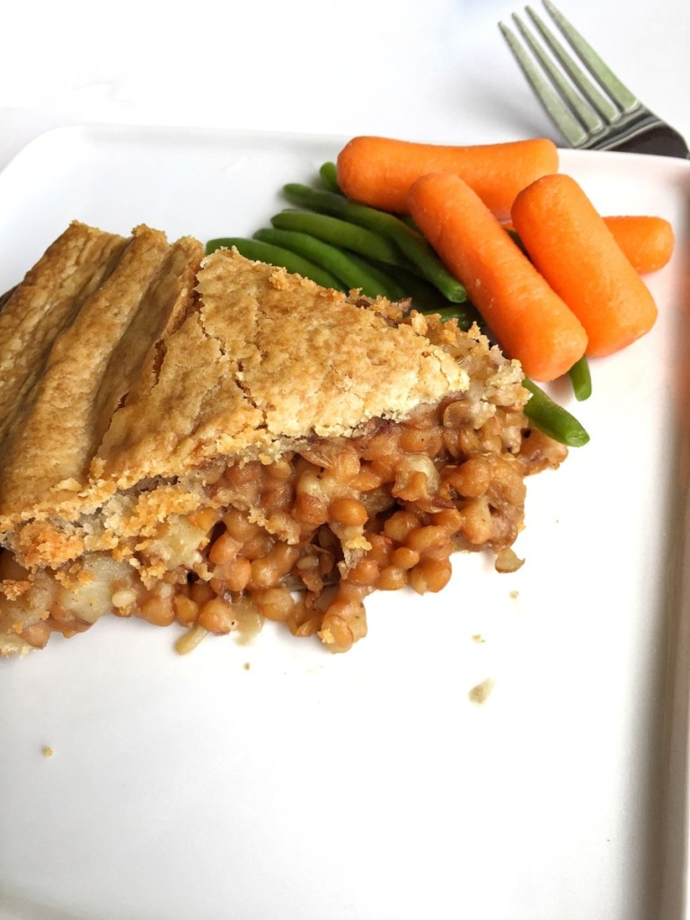 green lentil and potato filling, smothered in vegan gravy sauce on a white plate with a side of carrots and green beans