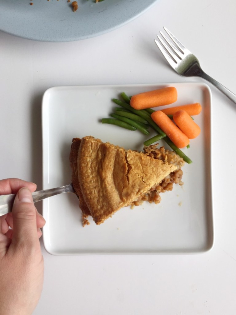 lentil pot pie shown with a slice on a white plate with a side of carrots and green beans