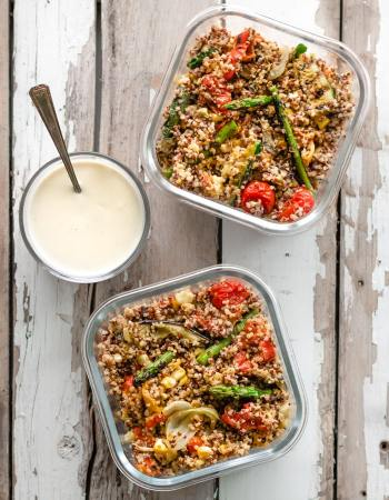 Quinoa salad with grilled veggies and tahini dressing shown served into two glass containers for lunch