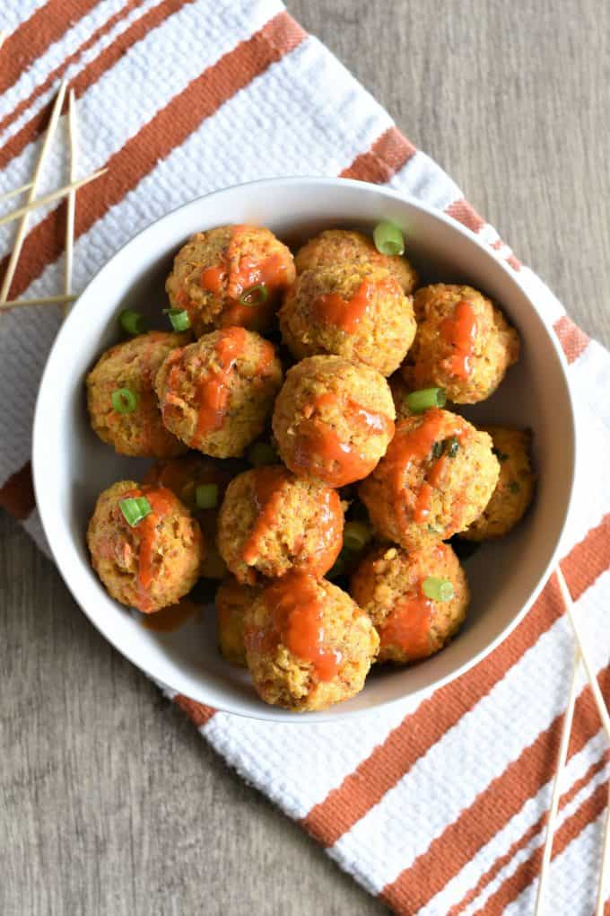 vegan buffalo chickpea meatballs in a white bowl sprinkled with green onion