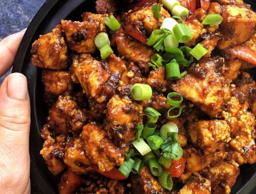 Crispy Tofu Chicken shown with bbq sauce sprinkled with green onions