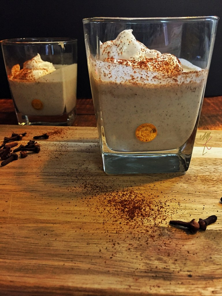 Vegan eggnog shown in a clear glass with cinnamon and nutmeg sprinkled on top.