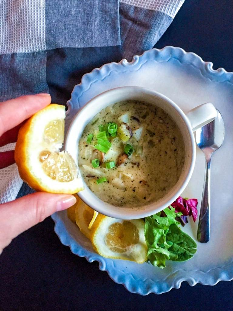 Vegan clam chowder soup in a white mug on a blue plate with lemon