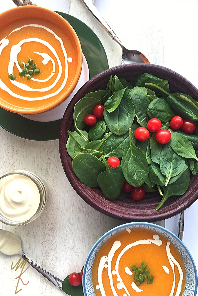 two bowls of butternut squash soup with a swirl of cashew cream