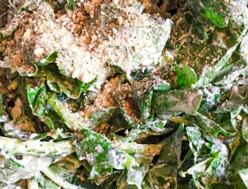 Image shows vegan kale caesar salad topped with vegan parmesan cheese in a large green bowl