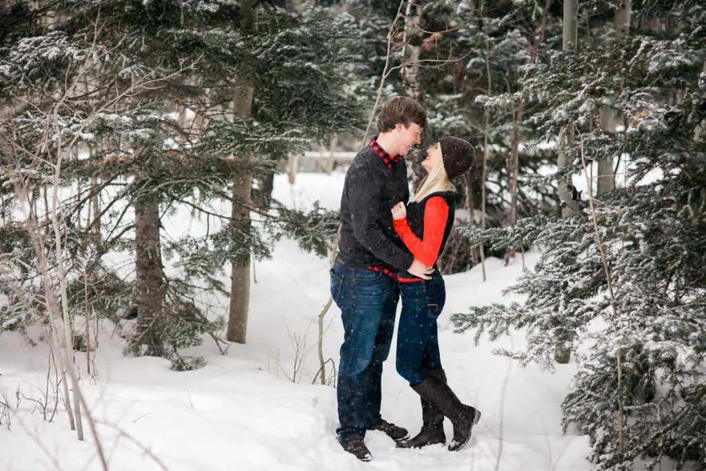 Winter Engagement photo in snowstorm under pine trees