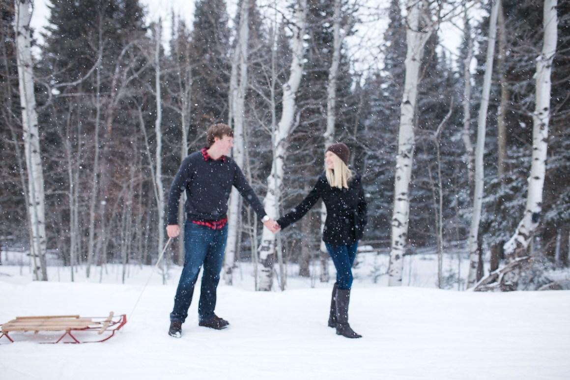 Engaged couple with vintage sled in Laramie wyoming