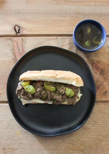 Italian Beef Sandwiches on a black plate, next to a small dish of broth.