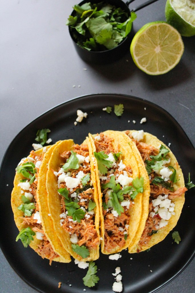 Slow Cooker Chicken Tacos topped with cilantro and cheese , on a black plate.