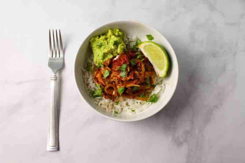 Bowl whit Chicken Tinga and rice. Topped whit Avocado.