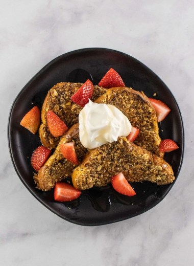Granola French Toast on topped with strawberies and whipped cream- black pate