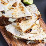 carnitas quesadilla on a wooden serving platter.