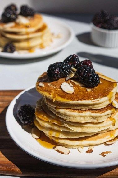 Almond Milk Pancakes topped with blackberries and almonds on a plate.
