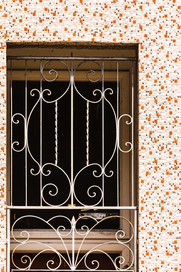 An iron screen gate to a doorway surrounded by a tile mosaic.