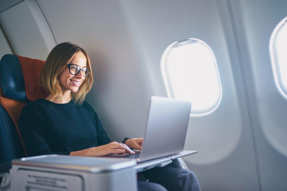 Mujer que trabaja en su computadora portátil mientras dentro del avión