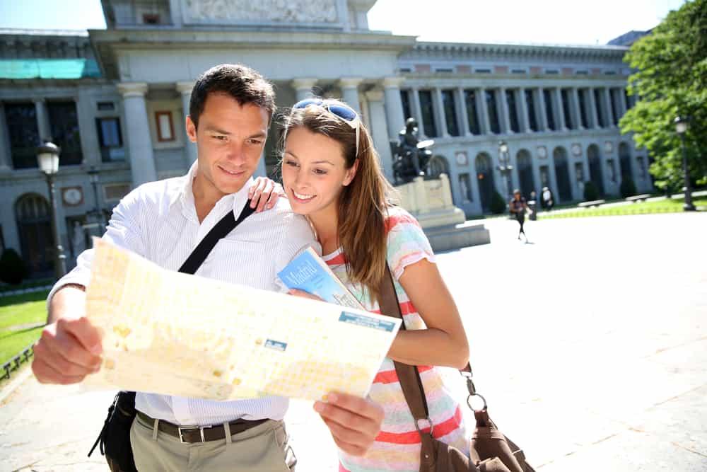 Pareja leyendo el mapa de la ciudad frente al museo del Prado, Madrid