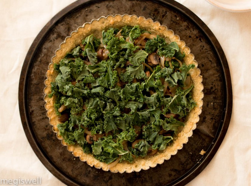Sautéed mushrooms, onions, and French cream make this Kale, Onion, and Mushroom Quiche creamy while the kale adds a slight crunch and a crumbly almond flour crust melts in your mouth. Perfect for breakfast, brunch, lunch, and dinner! | www.megiswell.com