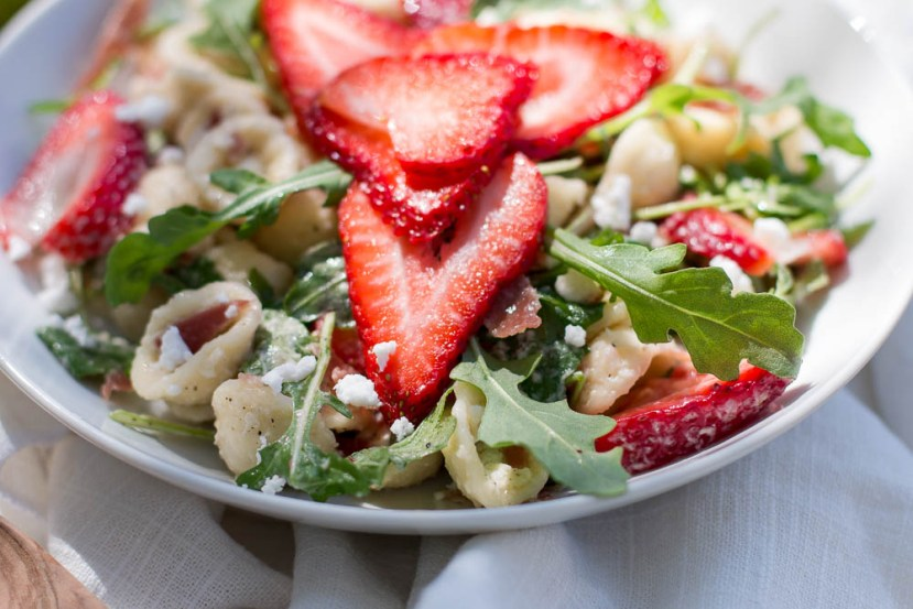 Close up view of orecchiette pasta, arugula, feta, and strawberry slices in a shallow white bowl.