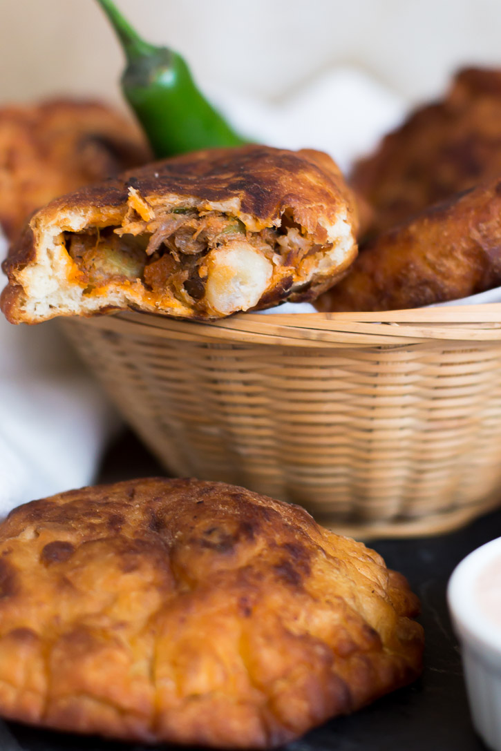 Use your leftover pulled pork for these Shredded Pork Empanadas. Fire roasted tomatoes and chilies in adobo sauce create a fiery sauce and poblano peppers add smoky flavor to the filling. Dip them in a delicious Adobo Aioli Dip made from the sauce. | www.megiswell.com