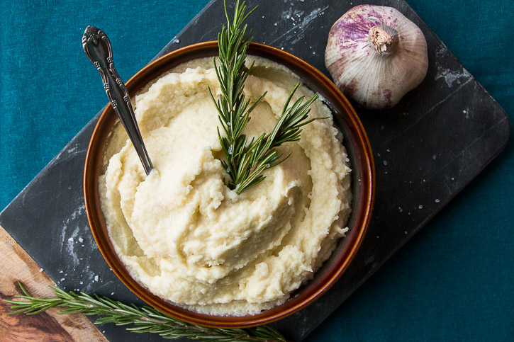 Cauliflower keeps this Creamy Garlic Cauliflower Potato Mash light while a little potato adds that satisfying creamy thickness of traditional mashed potatoes. Butter is infused with garlic to add amazing flavor to this Thanksgiving side dish. | www.megiswell.com