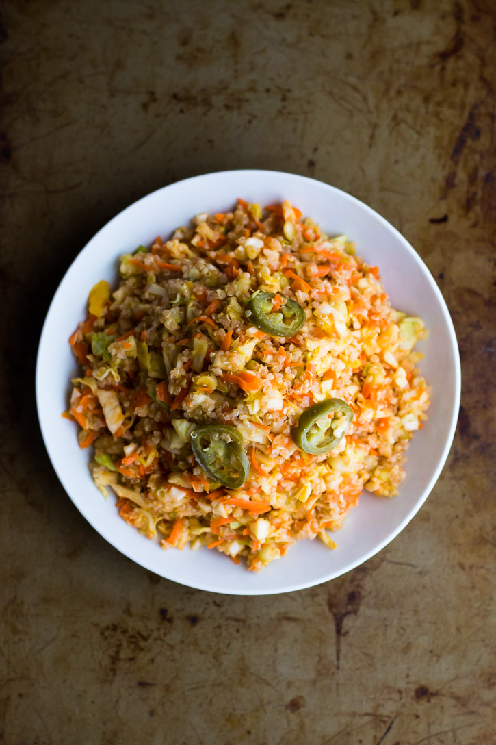 This easy and healthy Quinoa Slaw Salad with Honey Jalapeño Dressing is a healthier twist on traditional coleslaw. Finely diced and grated cabbage, carrot, and cucumber are tossed with quinoa and a sweet, spicy, and slightly tart dressing. | www.megiswell.com