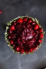 Overhead shot of Cranberry Pomegranate Sauce in a dish lined with fresh cranberries and rosemary sprigs.