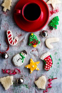 Overhead view of frosted Christmas cookies surrounded by bells, a coffee cup and saucer, and curled ribbon on top of a sprinkle covered clothe back round.
