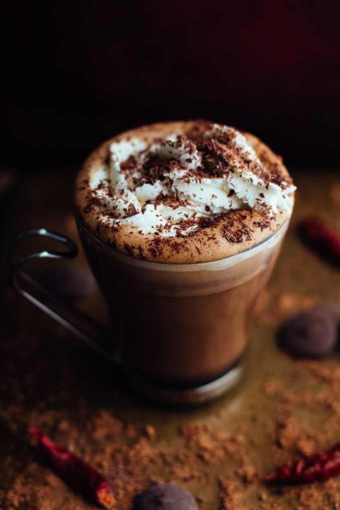 Slightly angled vertical view of glass mug with metal handle filled with hot chocolate, topped with whipped cream and chocolate shavings, and surrounded by cocoa powder, chocolate wafers, and dried chilies.