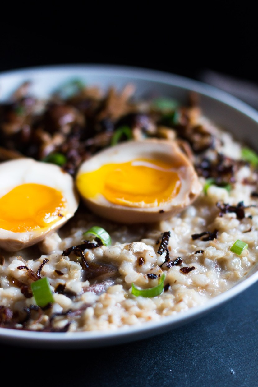 Very close vertical side shot of brown rice congee and two ramen egg halves with runny yolks.