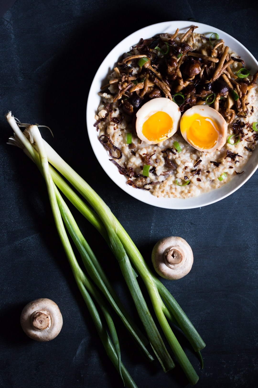 Overhead shot of a round bowl filled with congee, stir fried mushrooms, fried shallots, green onions, and a split ramen egg with runny yolks on a plain dark surface surrounded by two raw mushrooms and a green onion stalk.