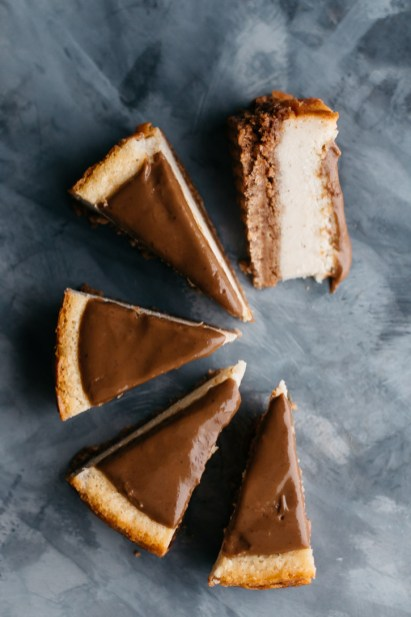 Overhead shot of cheesecake arranged in a fan shape with one slice laying on its side.