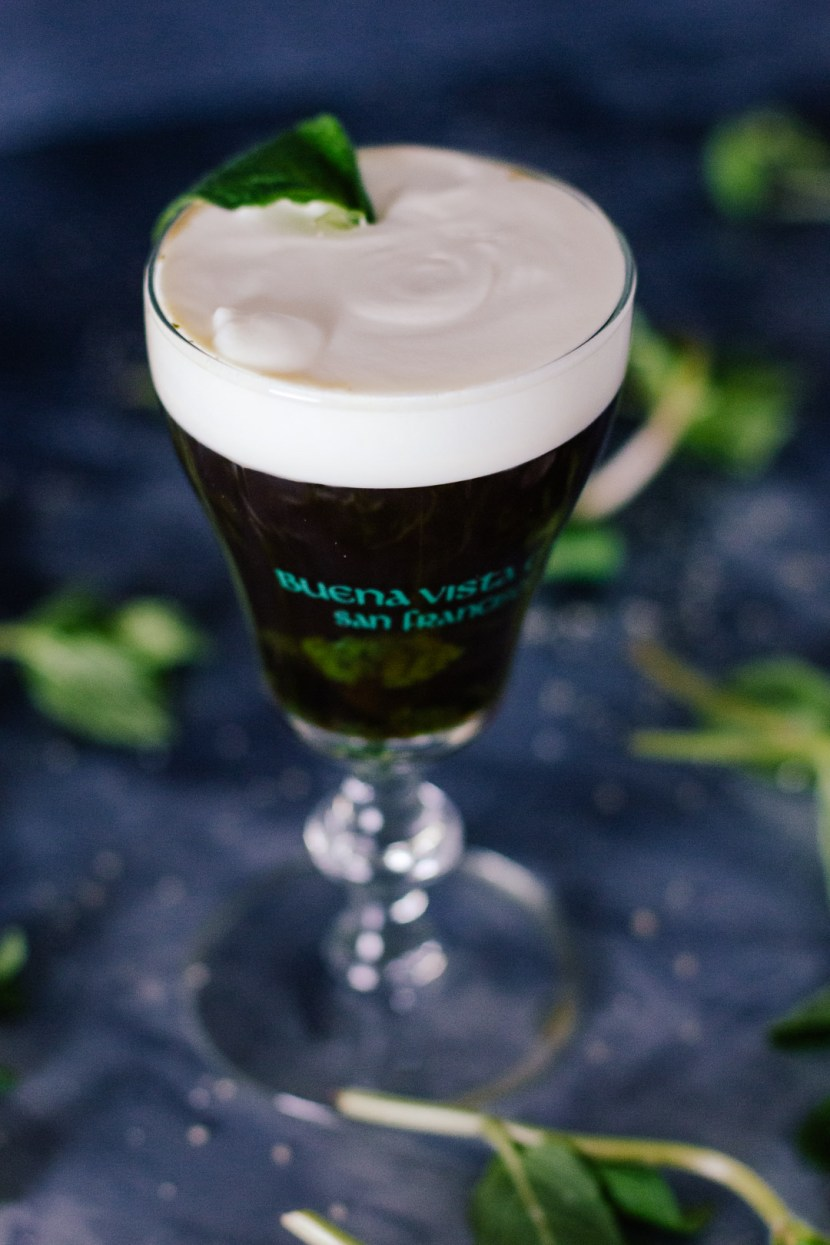 Vertical, slightly angled shot of an Irish Coffee topped with cream in a small glass goblet surrounded my mint leaves and grains of sugar.