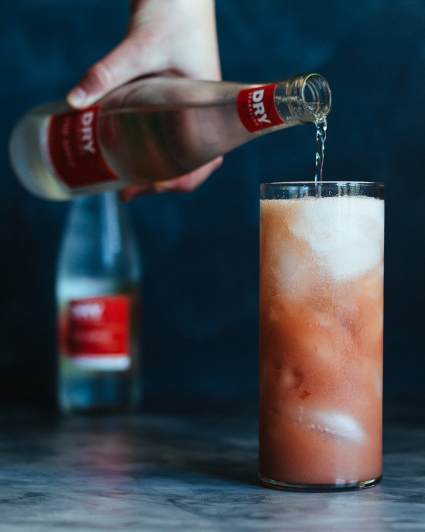 Vertical shot of a hand pouring sparkling dry soda into a tall glass filled with a Rhubarb Whiskey Collins beverage.